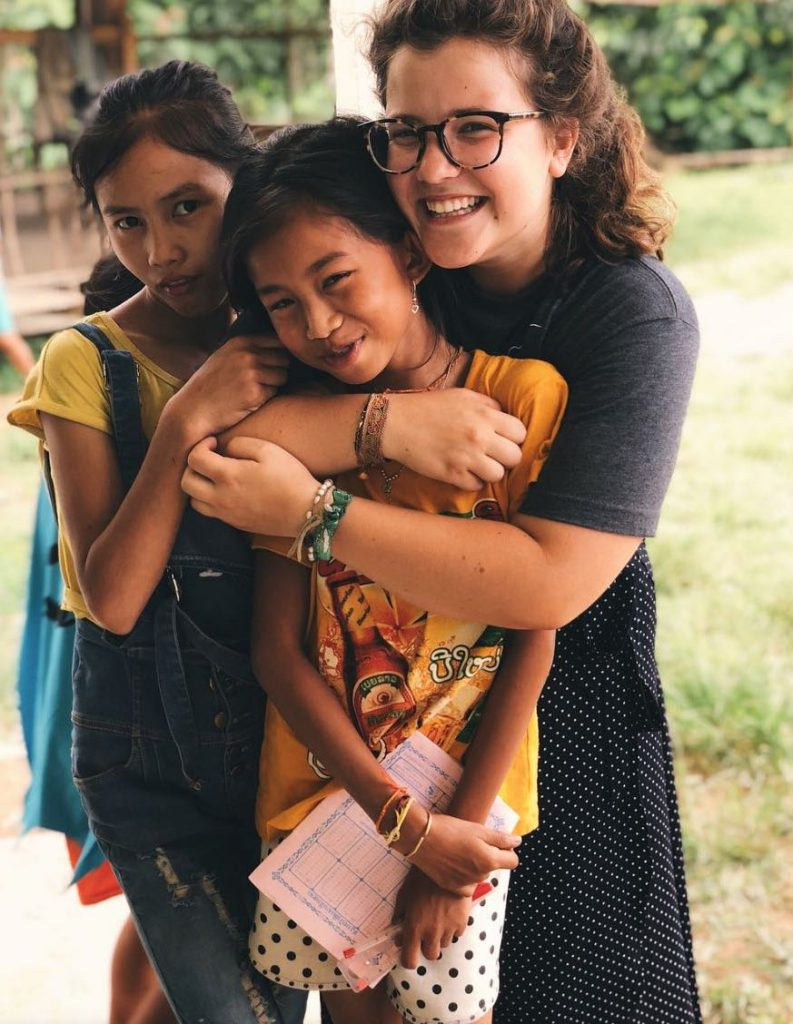 Photo of three girls hugging each other with two wearing yellow short sleeve shirts and the other wearing a grey one