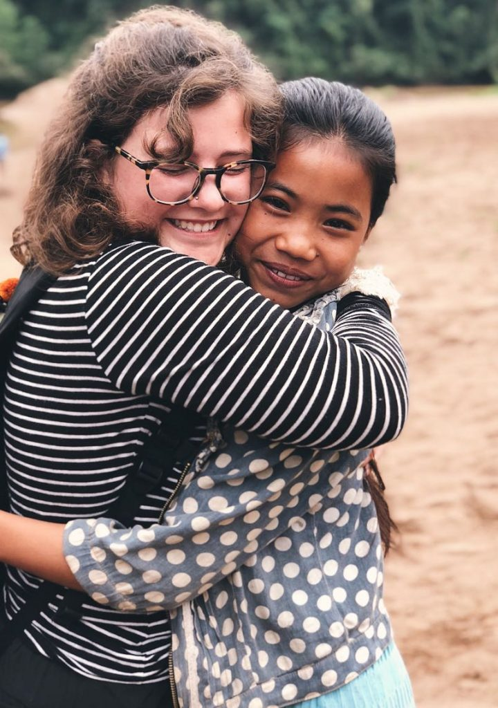 Photo of two girls hugging each other with left girl wearing a striped shirt and glasses and the right girl wearing a polkadot jacket