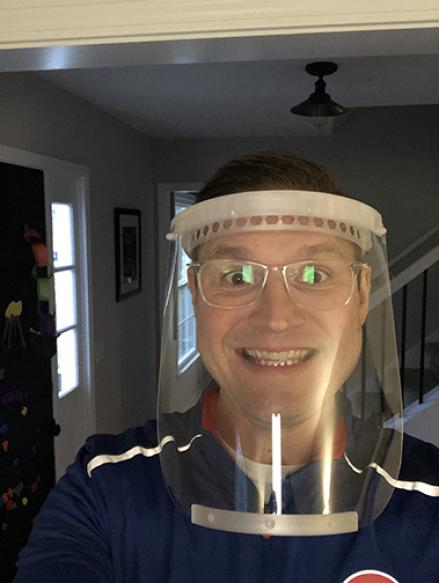 man wearing glasses and wearing a mask smiling at the camera