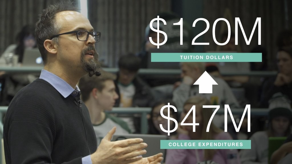 image of a man who's speaking to a lecture with numbers on tuition numbers