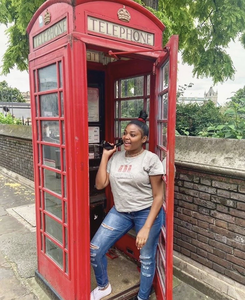 a woman in a bun, gray t-shirt, and jeans standing in a red telephone box