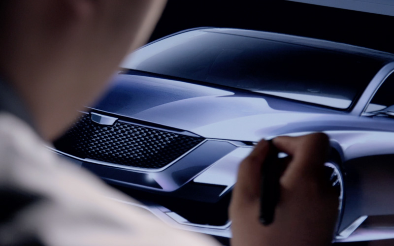 A man holds a digital pen drawing on a screen with the image of a silver concept car.