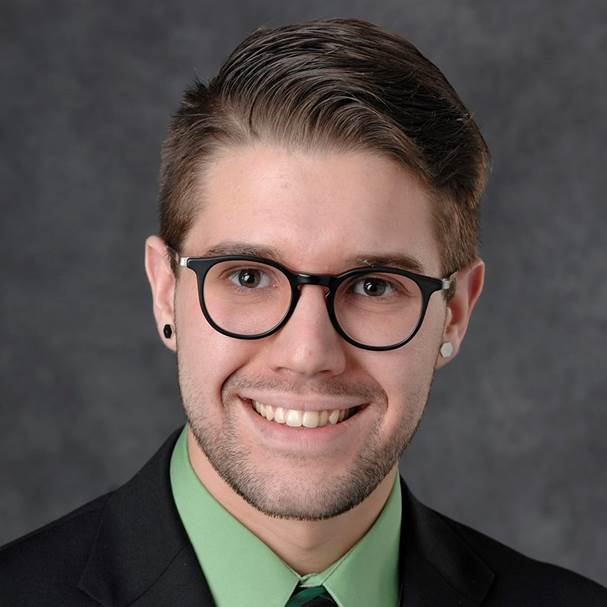 portrait of a man with brown hair wearing glasses and a green shirt with a black suit coat
