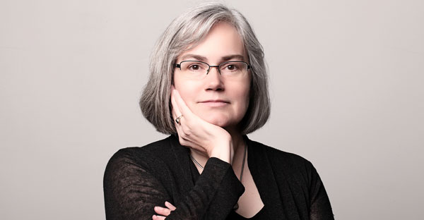 a women wearing glasses and wearing a black shirt