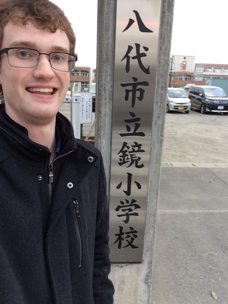 Josh Anderson next to a sign in Japanese