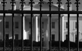 black and white photo of a fence with a house in the background