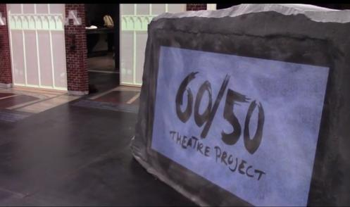 an image of a stone-like sign that says '60/50 theatre project'