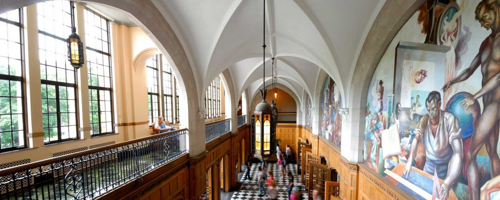 Panoramic photo of an auditorium. There are ceiling high windows to the left and a balcony. To the right is a mural.