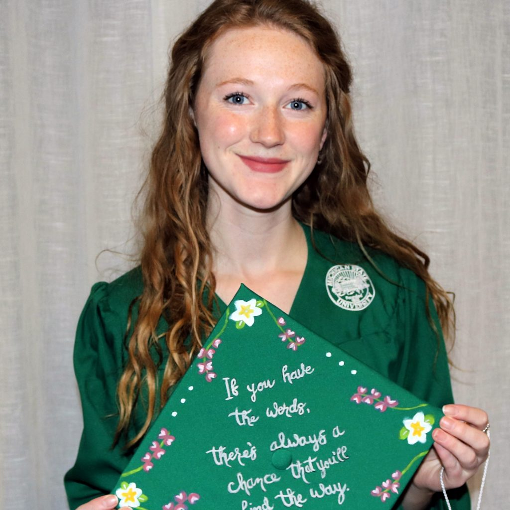 woman with red hair wearing a green graduation gown and holding a cap