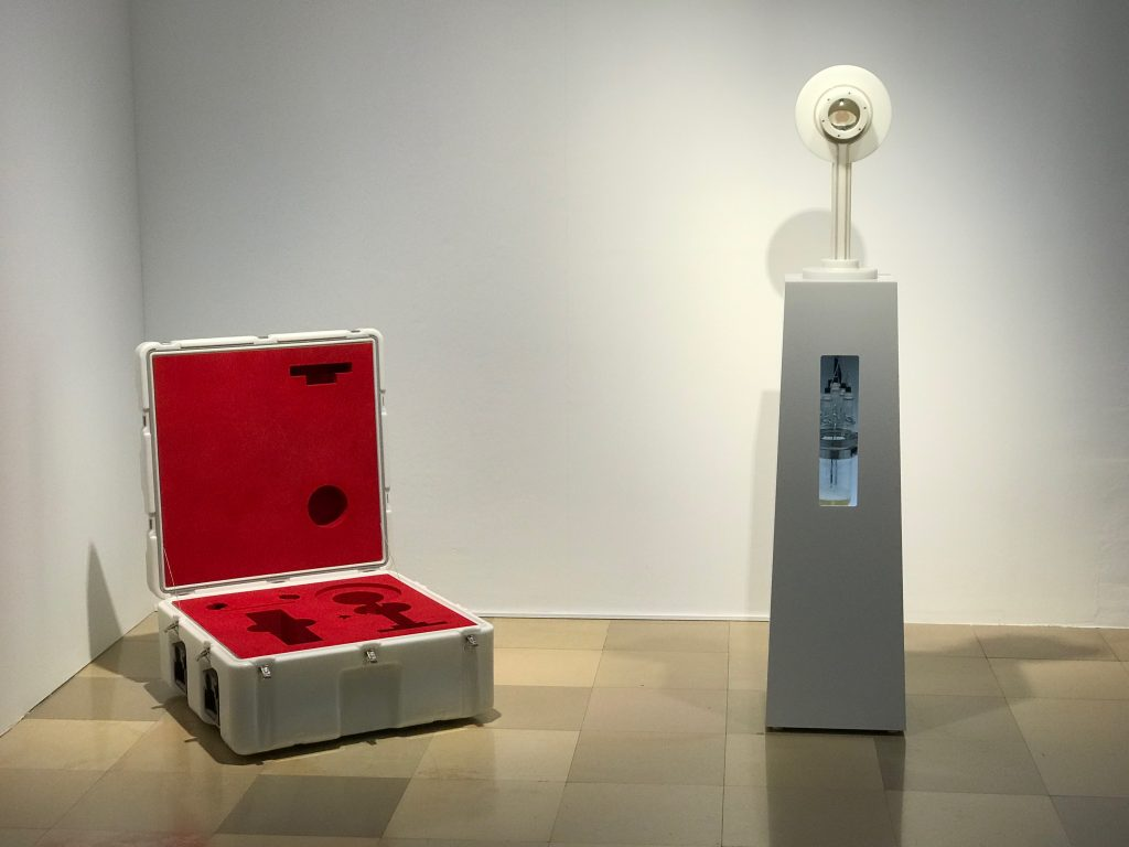 Art exhibit of a white box (left) lined with red padding. Next to it on the right is a white device with a circular part containing a magnified piece of bread in the center of the circle.