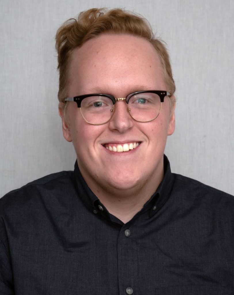 man wearing a black shirt with glasses smiling at the camera