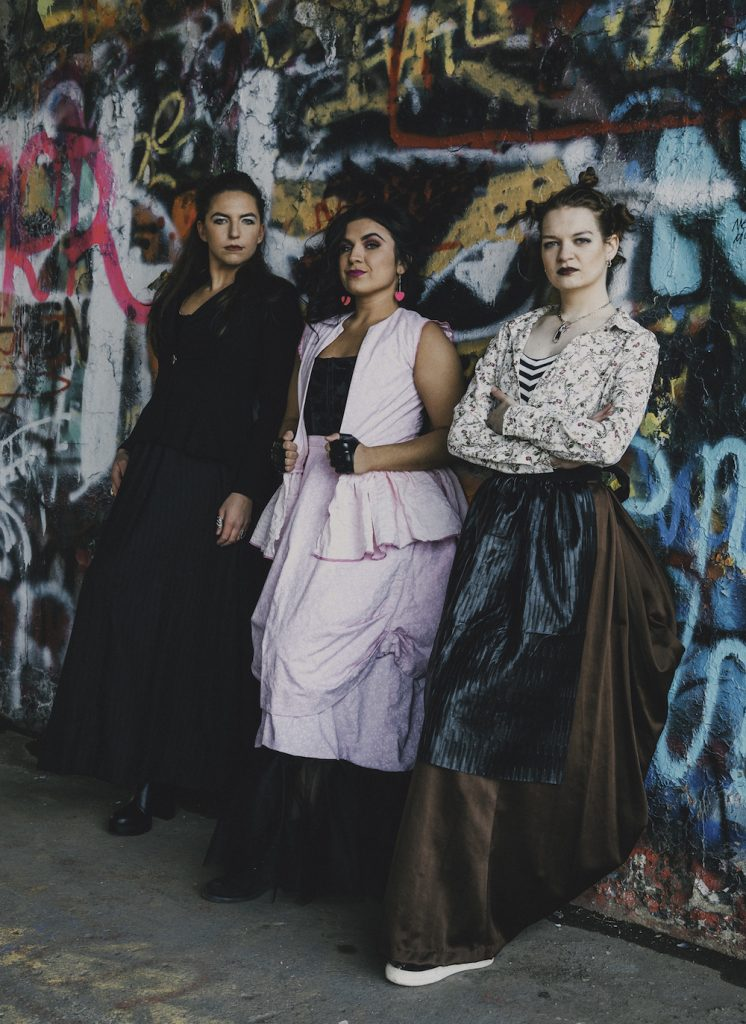 3 women standing against a colorful wall