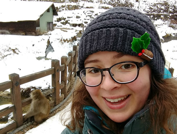 girl with winter hat and glasses standing in front of a snowy background and fence with a monkey on it