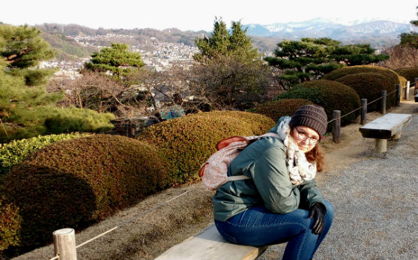 Girl wearing an olive green jacket and blue jeans with an orange backpack sitting on a bench in front of mountains and trees