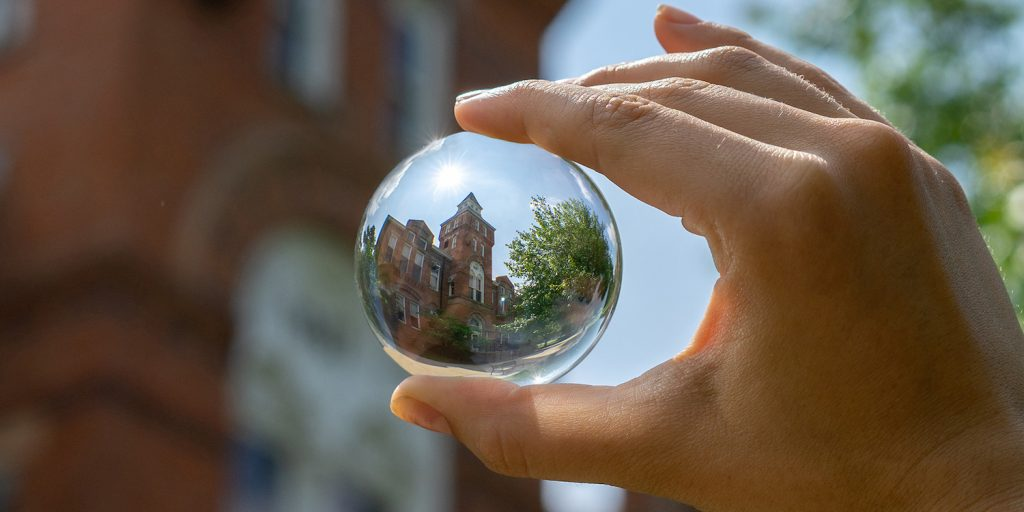 a hand holing a glass sphere where the brick building behind it can be seen in the sphere