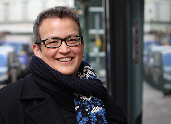 woman with glasses and a scarf smiling at the camera