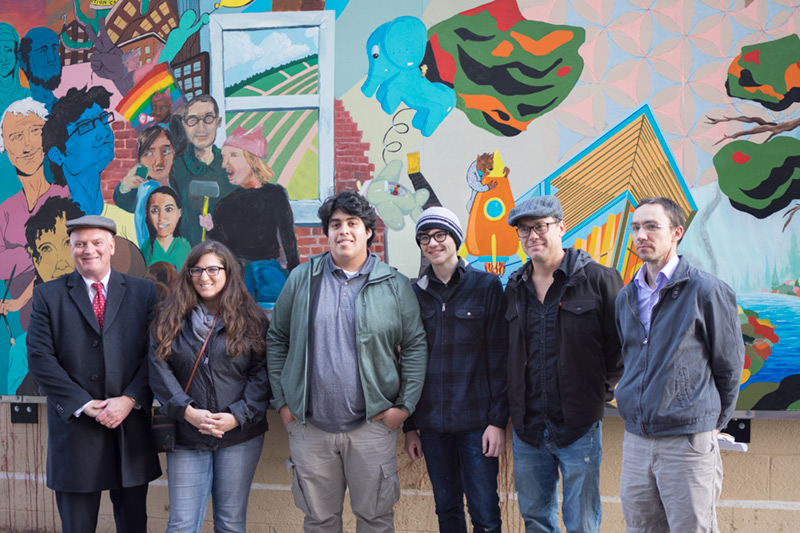 Six people standing in front of a brightly painted mural.