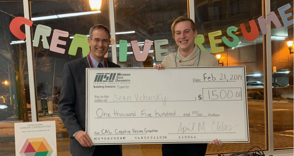 two people holding up a large board that resembles a check