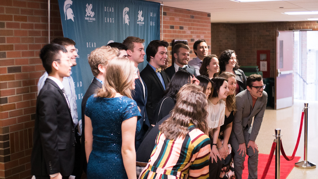"""Photo of a group of 20 people lined up in three rows taking a picture on a red carpet in front of a brown brick wall and a green tarp that says """"Dead Ends"""" on it and a white spartan head"""
