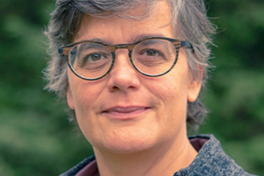 Woman with short gray hair and black rimmed glasses