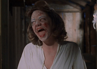 Still of woman wearing white and red face paint screaming