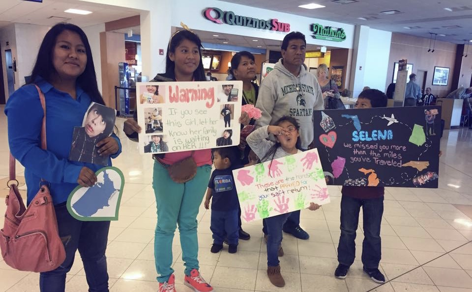 picture of a family waiting at an airport and holding up signs for who they are waiting for