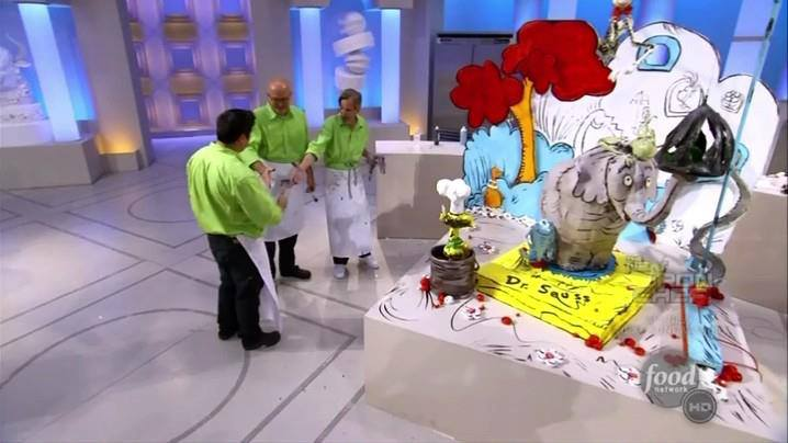 three people who are all wearing green shirts and white aprons who are standing in front of a large life-like Dr. Seuss cake