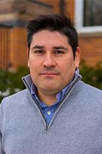 a man with short dark hair wearing a light blue shirt and sweater