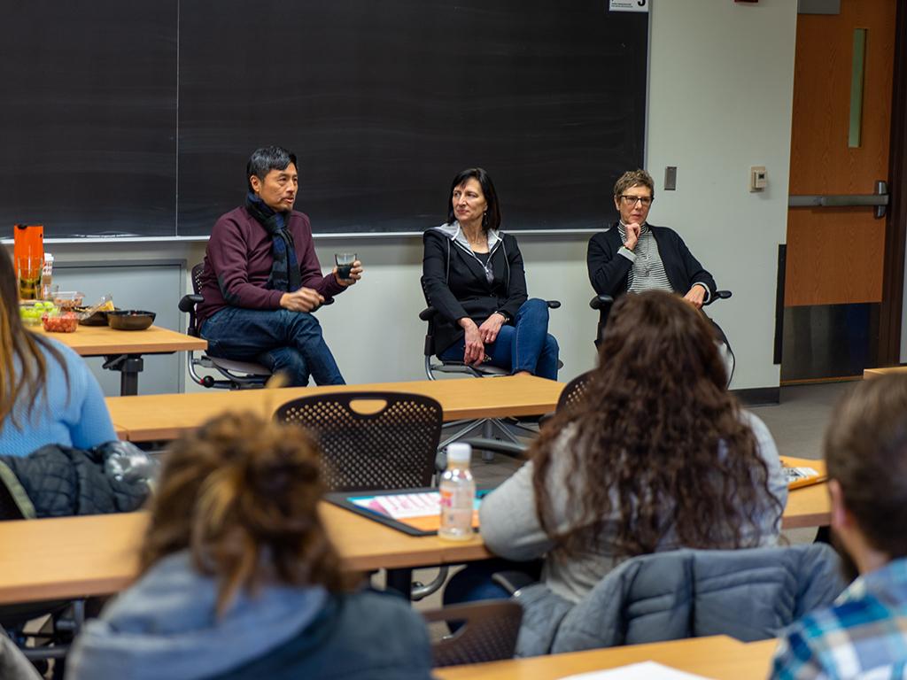 three adults talking towards a class full of students