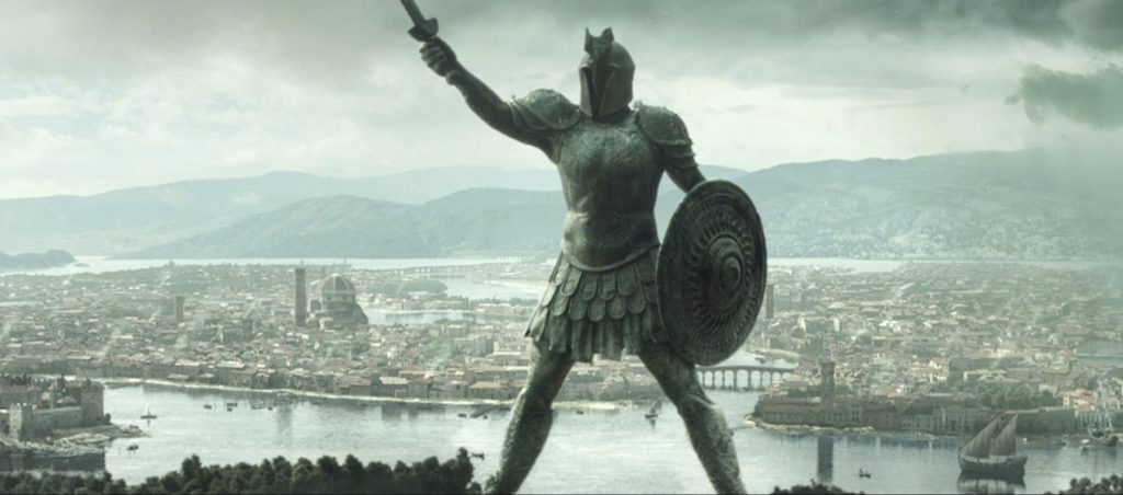 a large warrior statues stands with a shield and sword. Behind it is a large city near the water.