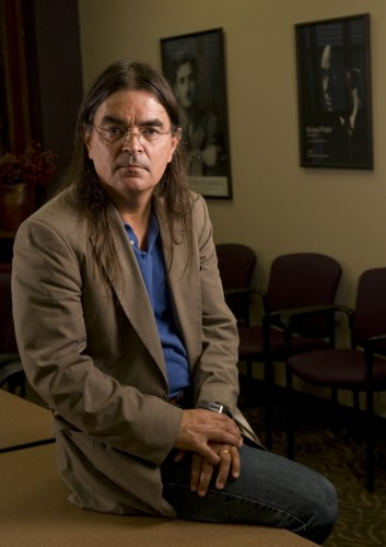 Man with long brown hair and glasses is wearing a brown blazer and blue shirt. He is sitting on a wooden desk with his hands folded over his lap