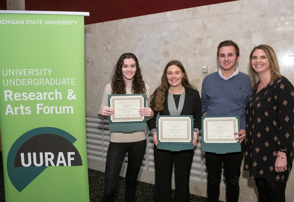 Photo of four people standing next to each other with the left three people holding certificates