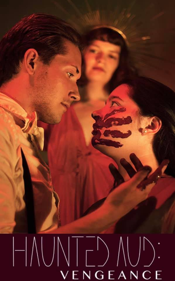Side view of a man and woman looking at each other with a deity looking over them. The woman has a red handprint on her cheek and the man has red on his hands