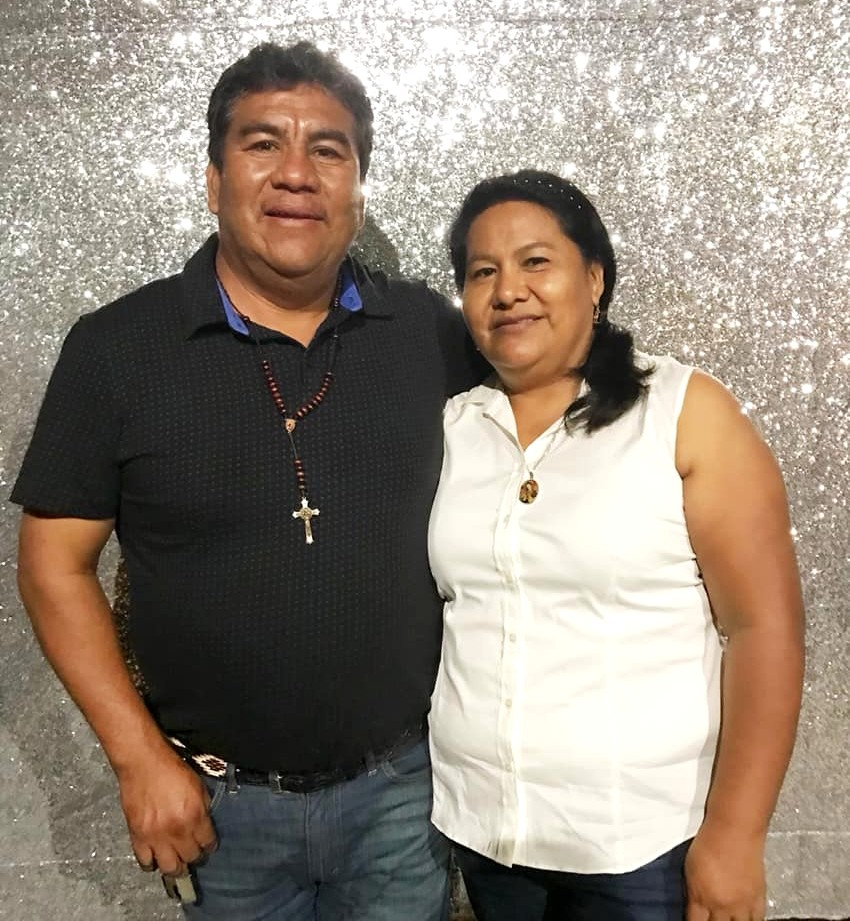 picture of a man(left) and woman(right), the man has black, spiky hair and is wearing a black polo, jeans, and a cross necklace. The woman has a black, low ponytail and is wearing a sleeveless white shirt and black pants