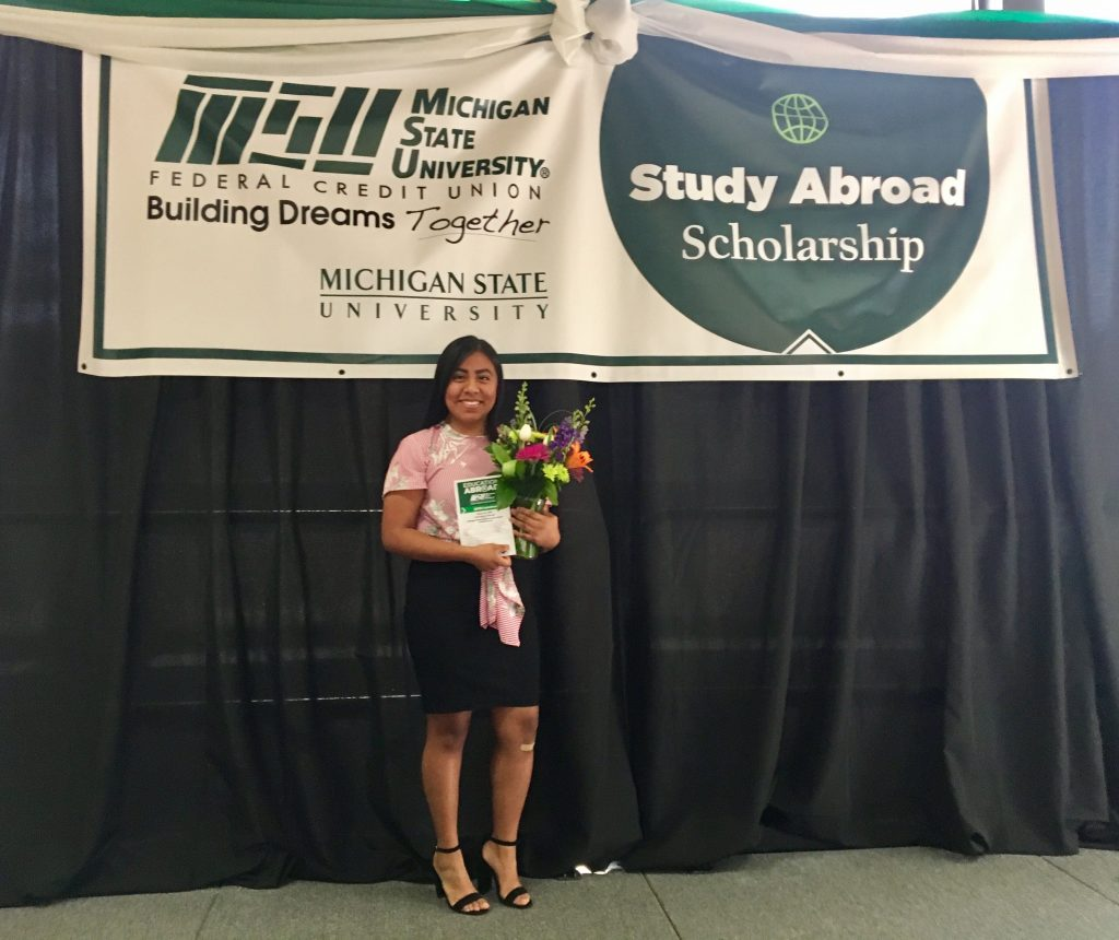A woman holding a bouquet  on a stage with a poster that reads 'Study abroad scholarship'