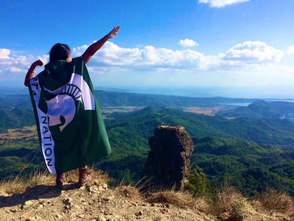 woman posing on a hill with her back to the camera, she has a spartan flag tied to her