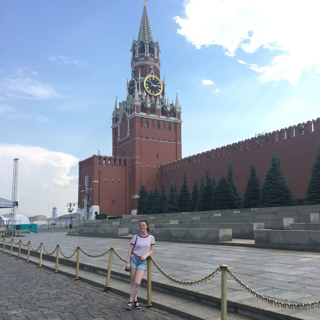 picture of a girl in a ponytail posing in front of a Russian, red brick building