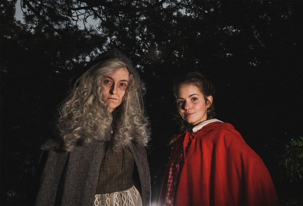 two women in costumes standing next to each other in the woods