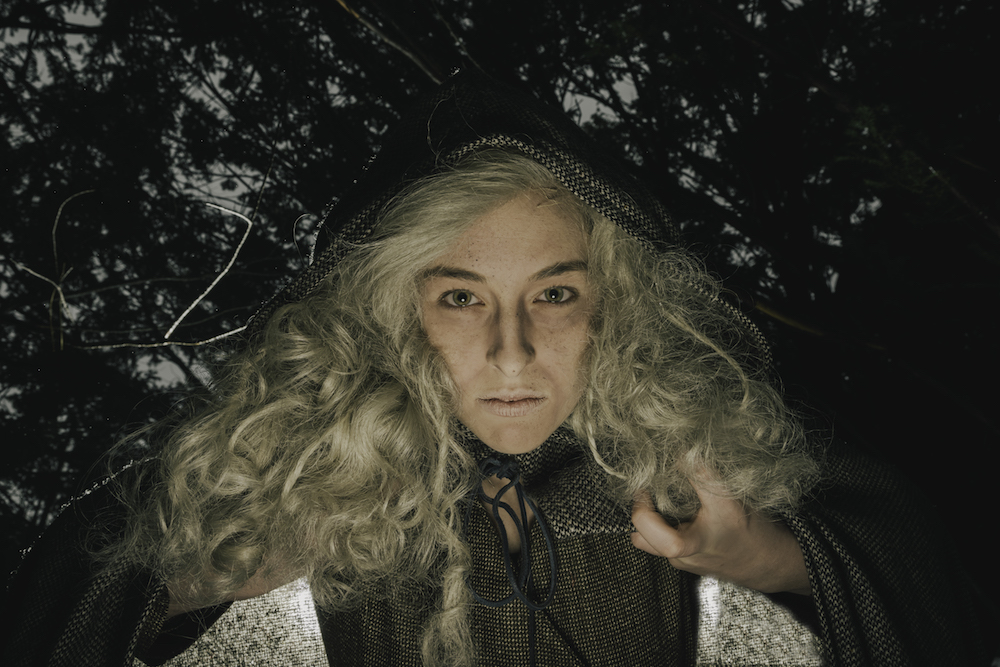 Girl wearing a witch costume (grey wig, dress, hooded cape)