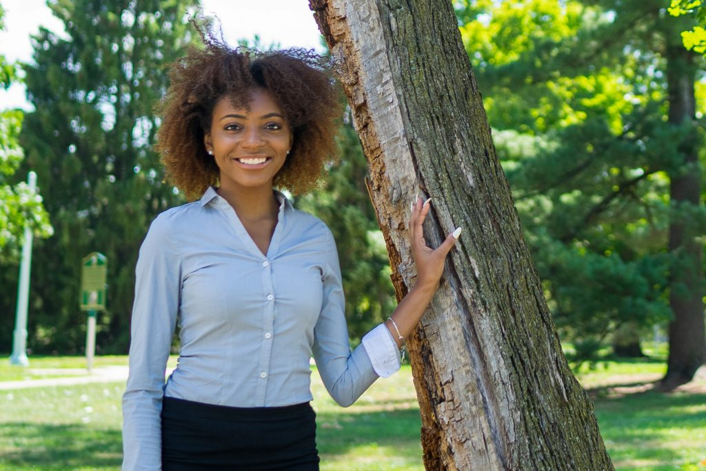 picture of a woman in a light blue button-up, smiling with a hand resting on a tree
