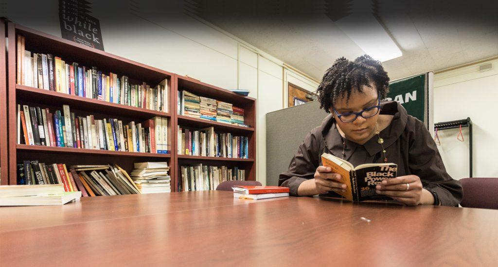 Joyce-Zoe Farley reading at desk