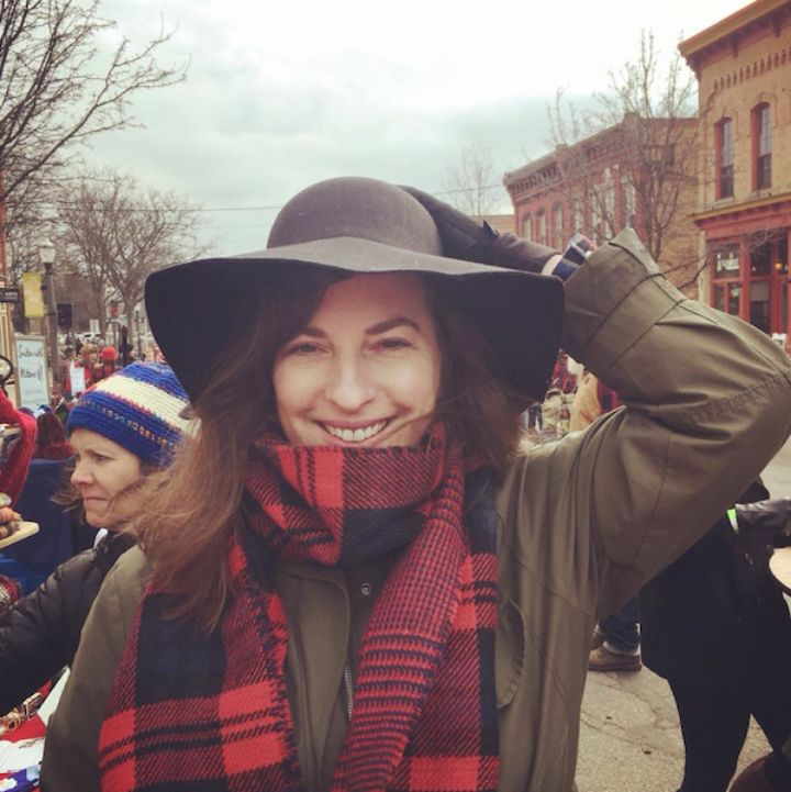 a women with brown hair wearing a hat, a army green coat and a red and black scarf