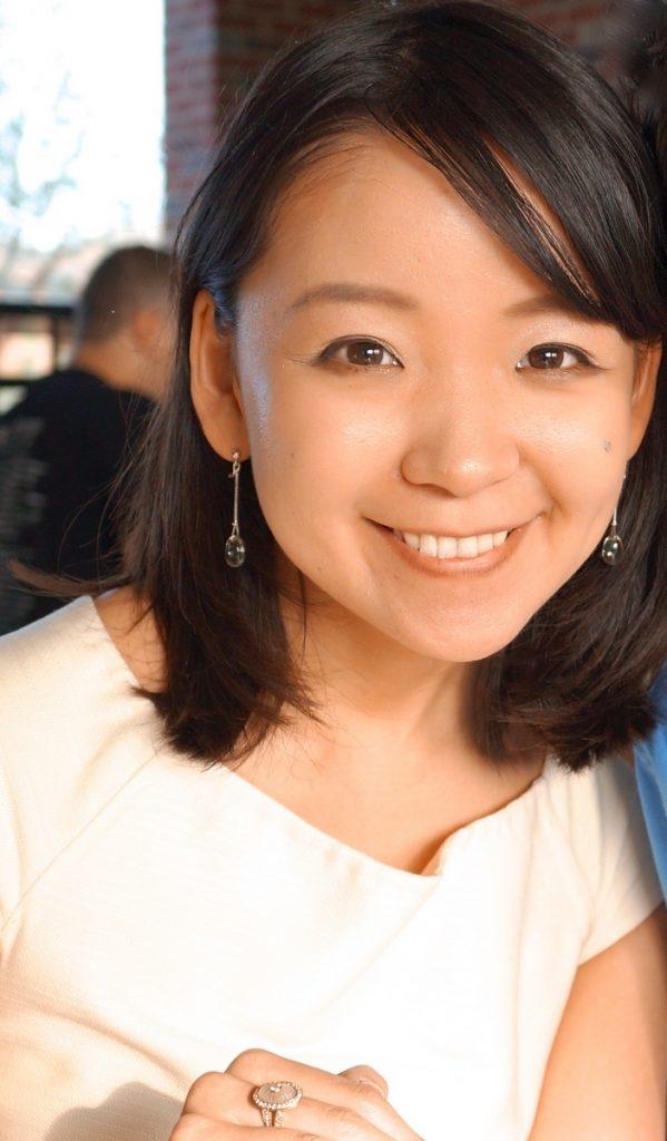 a women with short dark hair wearing a pink shirt