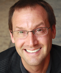 a man with short brown hair wearing glasses and a black shirt