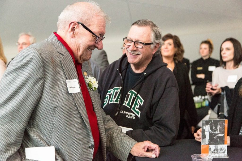 Two man standing next to each other smiling while having a conversation with left wearing checkered blazer with red shirt and glasses and right man wearing black sweatshirt with green writing and glasses