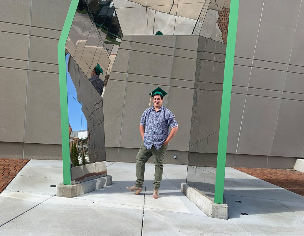 picture of a man in a blue button-up and standing in the center of a mirrored structure