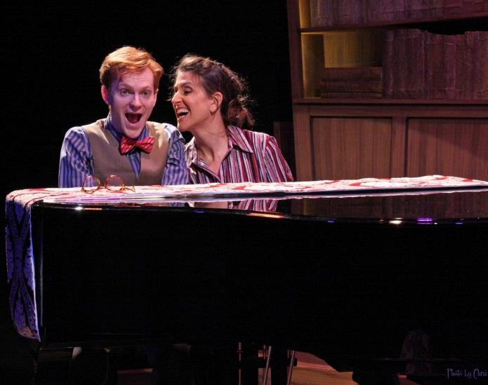 woman who's wearing a striped red shirt and looking at a man who's wearing a blue striped shirt, vest, and red bow tie. The pair is sitting at a black piano.