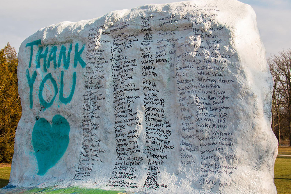 """Large rock painted white with a list of names next to the words """"thank you"""" in teal"""
