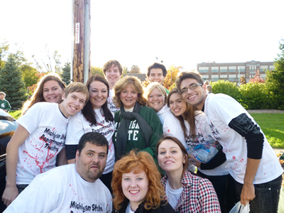 Group of students wearing white shirts with red paint surrounding a woman wearing a green sweatshirt