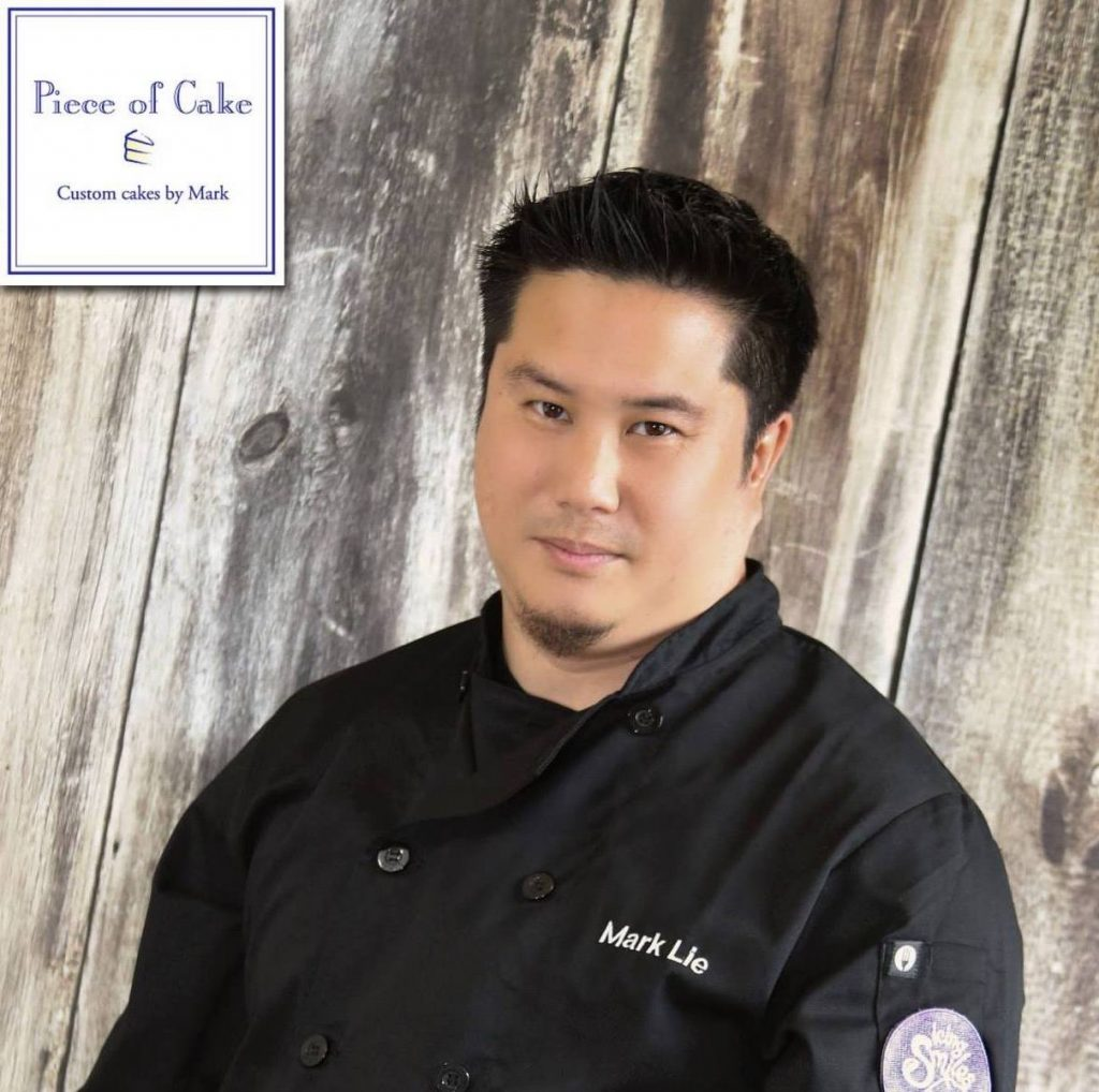 man who is wearing a black chef's shirt in front of a wooden wall